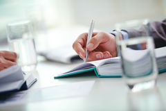 Writing lecture. Male and female hands making notes or writing working plan Stock Photos