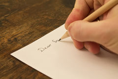 Writing a letter. A close photo of a persons writing a letter with a pencil Royalty Free Stock Image