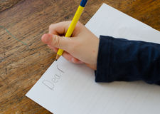 Writing a letter. Child writing a letter starting with Dear Stock Image
