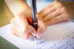 Writing a Letter. Girl Writing down a letter on a white sheet of paper with a black pen Royalty Free Stock Photography