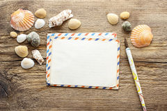 Writing a letter from holiday. Seashelles on a wood Royalty Free Stock Photo