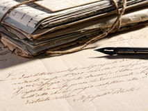 Writing a letter with a retro fountain pen. Writing a letter concept with a retro fountain pen lying on a faded old letter and a stack of vintage aged and worn Stock Image