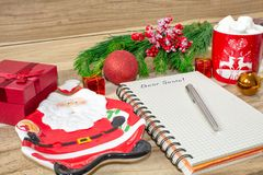 Writing a letter to Santa Claus on a wooden background with Christmas gifts, a plate in the shape of Santa Claus, a mug of marshma stock photography