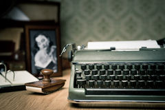 Writing a letter on vintage typewriter. Vintage typewriter on a wooden desk with old frame and picture on background stock photo