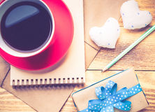 Writing love confession. Blank notepad coffee cup and love hearts on wooden table Stock Image