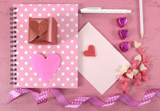 Writing love letters and cards for Happy Valentines Day. With heart shape candy on pink shabby chic wood background Royalty Free Stock Image