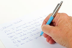 Writing love phrases on a paper with a pen. Writing love phrases on a paper with a blue pen Royalty Free Stock Photos