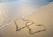 Writing love symbol. On the sand at a sea stock photos