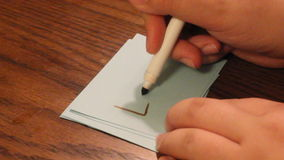 Writing love. Young women`s hand writing the word love on a white card stock video footage