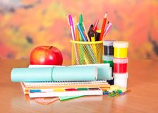 Writing materials, paints and apple Royalty Free Stock Images