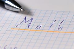 A writing math lesson on square paper with blue pen. Ideal for noughts and crosses game stock image