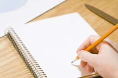 Writing a memo. Hand holding a pencil over a blank notepad page Royalty Free Stock Photography