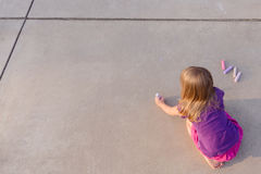 Writing a message for you. A young girl writing with chalk on white pavement. Designed as a graphic to place your own message for greeting card, advertisement Royalty Free Stock Photos
