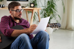 Writing music composition. Young man with guitar writing music composition Royalty Free Stock Photography
