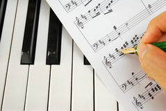 Writing on music score with pen on piano keyboard Stock Photo