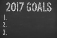 Writing New Year Goals on Chalkboard Background Stock Images