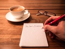 Writing new years resolutions and goals on a notepad royalty free stock image