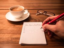 Writing new years resolutions and goals on a notepad stock image