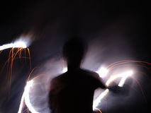 Writing in the Night with Fire. A young man makes designs in the night with a sparkler Stock Photography