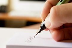 Writing a note. Hand holding a pencil. Shallow focus and low ISO Royalty Free Stock Photo