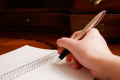 Writing a Note. A hand writing on a pad of paper on a wooden desk Royalty Free Stock Photos
