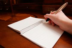 Writing a Note. A person's hand writing a note on a wooden desk Stock Image