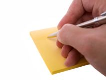 Writing a note. Writing a note on a block of sticknotes stock photo