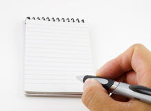 Person writing a note. Hand of a person with a pen about to write a message on an empty notepad with copy space stock photo