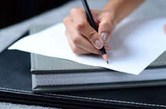 Writing a note. On paper Stock Images