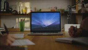 Writing note on paper. view5. Focus on ios( ux ) monitor macbook. wide angle of writing a text on paper. In the picture you can see the focus macbook monitor in stock footage