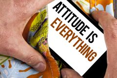 Writing note showing  Attitude Is Everything. Business photo showcasing Motivation Inspiration Optimism important to succeed writt. En Mobile Screen holding by Stock Images