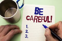 Writing note showing  Be Careful. Business photo showcasing Caution Warning Attention Notice Care Beware Safety Security written b. Y Man Notebook Paper Holding Royalty Free Stock Photos