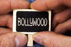 Writing note showing Bollywood. Business photo showcasing Indian cinema a source of entertainment written on Wood Piece holding by. Writing note showing Stock Image