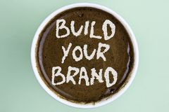 Writing note showing Build Your Brand. Business photo showcasing create your own logo slogan Model Advertising E Marketing writte. N Coffee in a Cup the plain royalty free stock photos