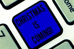 Writing note showing Christmas Is Coming. Business photo showcasing annual Christian festival celebrating Christs birth. Here Keyboard key Intention to create stock images