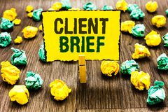Writing note showing Client Brief. Business photo showcasing A documents bounded by the terms of clients and the agency Clothespin. Holding yellow note paper royalty free stock photography