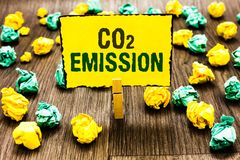 Writing note showing Co2 Emission. Business photo showcasing Releasing of greenhouse gases into the atmosphere over time Clothespi. N holding yellow note paper royalty free stock photos
