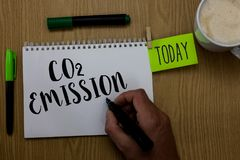 Writing note showing Co2 Emission. Business photo showcasing Releasing of greenhouse gases into the atmosphere over time Man holdi. Ng marker notebook clothepin royalty free stock images