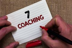 Writing note showing 7 Coaching. Business photo showcasing Refers to a number of figures regarding business to be succesful Man's. Hand hold white paper with royalty free stock images