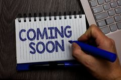Writing note showing Coming Soon. Business photo showcasing something is going to happen in really short time of period Man holdin. G marker spiral notebook royalty free stock photo