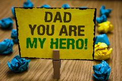 Writing note showing Dad You Are My Hero. Business photo showcasing Admiration for your father love feelings compliment. Paperclip grip yellow page with text royalty free stock image