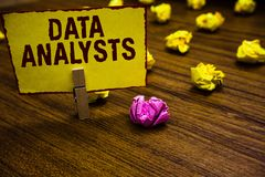 Writing note showing Data Analysts. Business photo showcasing Programmer Design and Create Report Identifies patterns. Clothespin holding yellow paper note stock photo