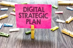 Writing note showing Digital Strategic Plan. Business photo showcasing creat schedule for marketing product or brand Multiple clip. S woody table small card Stock Image