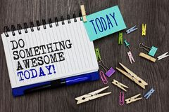 Writing note showing Do Something Awesome Today. Business photo showcasing Make an incredible action motivate yourself Different p. Aperclip on woody table pinch Stock Image