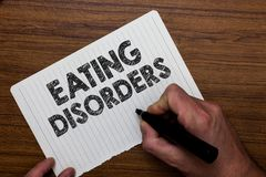 Writing note showing Eating Disorders. Business photo showcasing any of a range of psychological abnormal food habit. S Man holding marker notebook paper stock image
