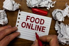 Writing note showing Food Online. Business photo showcasing asking for something to eat using phone app or website Man holding mar. Ker notebook page crumpled Stock Photo