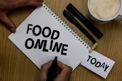 Writing note showing Food Online. Business photo showcasing asking for something to eat using phone app or website Man holding mar. Ker notebook clothepin Royalty Free Stock Photos