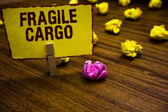 Writing note showing Fragile Cargo. Business photo showcasing Breakable Handle with Care Bubble Wrap Glass Hazardous Goods Clothes. Pin holding yellow paper note stock photo