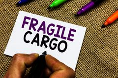 Writing note showing Fragile Cargo. Business photo showcasing Breakable Handle with Care Bubble Wrap Glass Hazardous Goods Man han. D holding marker white paper royalty free stock photos