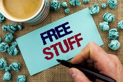 Writing note showing Free Stuff. Business photo showcasing Complementary Free of Cost Chargeless Gratis Costless Unpaid written b. Y Man Holding Pen Sticky Note royalty free stock photos